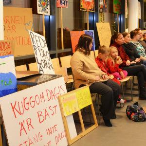 Flera personer sitter på stolar i en skolmatsal. Bredvid dem står skyltar där det står till exempel Redda byskolorna.