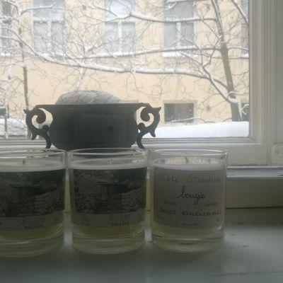 tre doftljus i rad på ett fönsterbräde