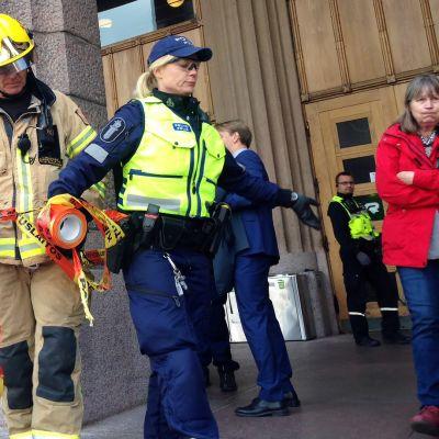Poliisi vetää pelastuslaitoksen teippiä sulkeakseen pääsyn Helsingin rautatieasemalle.
