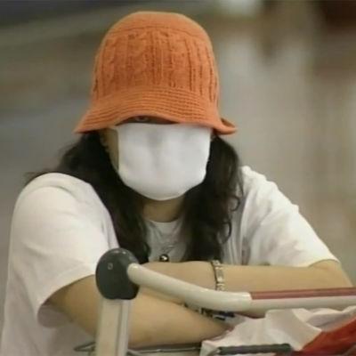 Nainen suojautuneena hengitysmaskiin Kiinassa 2003 SARS-epidemian aikaan
