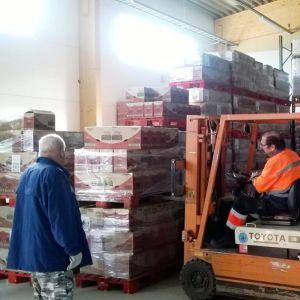 En truck flyttar varor i en lagerhall. En man i förarhytten, en annan tittar på.