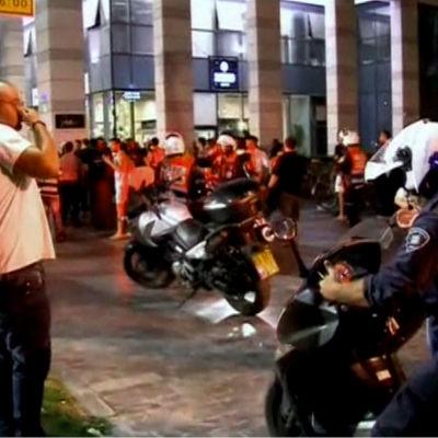 Motorcykelpolis och civilpersoner utanför brottsplats i Tel Aviv.