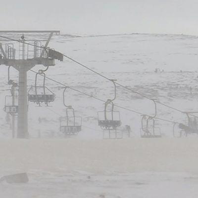 Snöigt landskap med skidliftar.
