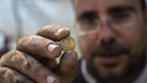 I förgrunden syns en hand som håller upp ett uråldrigt guldmynt. I bakgrunden en man med glasögon och skägg.