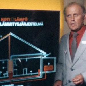 Oranssiin kauluspaitaan ja harmaaseen takkiin pukeutunut mies esittelee aurinkolämmitysjärjestelmää taulun avulla.