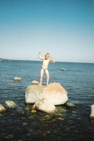 Juontaja Tom Nylund lapsena tasapainoilee suurella kivellä Itämeressä
