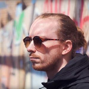 Närbild på man med långt rött hår och solglasögoni profil. Han lutar sig mot en vägg med graffiti.