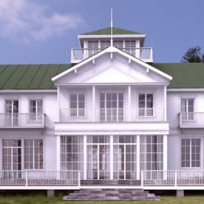 Ett vitt hus i trä med grönt tak.