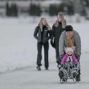 Personer som är ute och går och åker på isen en kall vinterdag.