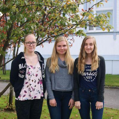 Kuvassa kolme lukiolaista puun edessä.