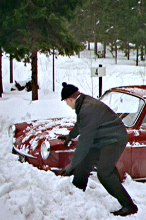 Mies lapioi autoa lumesta valistusfilmissä Turvallista talviajoa (1966)