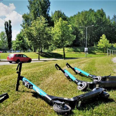 Sähköpotkulaudat makaavat nurmikolla tien varressa.