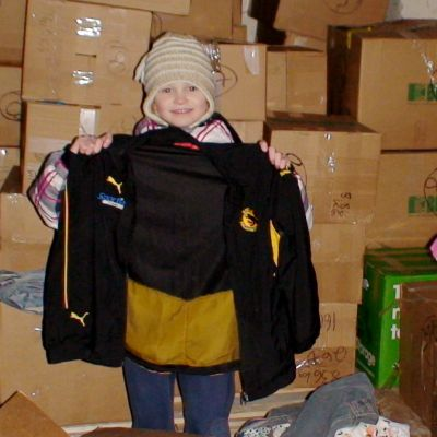 Tyttö pitää takkia kädessään pakolaisleirillä