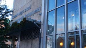 Texten Raseborgs stad Raaseporin kaupunki på stadshuset i Ekenäs centrum. Stadens vitsippsvapen skymtar bakom grankvistar.
