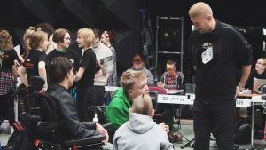 Regissören Marco Bjurström samtalar med några ungdomar under repetitionerna av Prinsessa Ruusunen - paluu tulevaisuuteen.