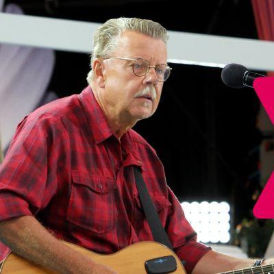 Mikael Wiehe står framför en mikrofonställning och spelar akustisk gitarr.