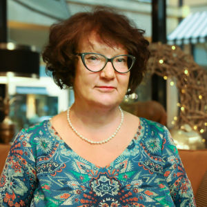 Monika Fagerholm tittar in i kameran. I bakgrunden syns en soffa och lampor.