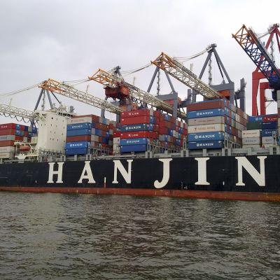 Kuvassa erivärisiä rahtikontteja meressä olevassa laivassa ja niiden päällä nostotelineitä.