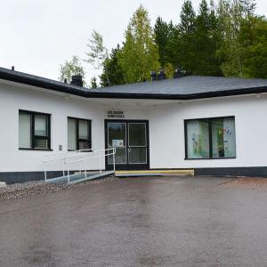 Ett vitt hus med svart tak. Ovanför dörren finns en skylt där det står hälsogård terveystalo.