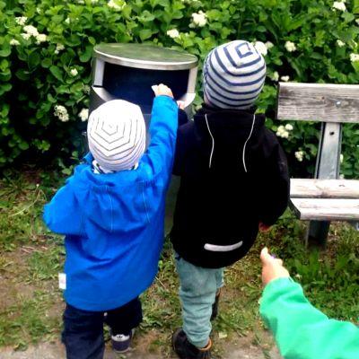 Lapset vievät roskia puhuvaan roskapönttöön.