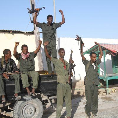Viisi sotilasta kädet ylhäällä.