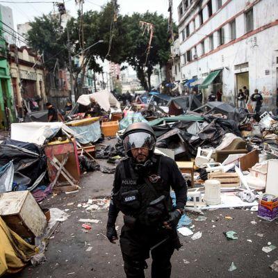 Kypäräpäinen poliisi kävelee kadulla joka on aivan täynnä huonekaluja ja romua.