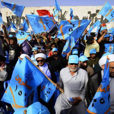 Mihiä käsissään sinisiä lippuja.