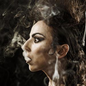 Tummatukkainen nainen puhaltaa tupakan savua suustaan.