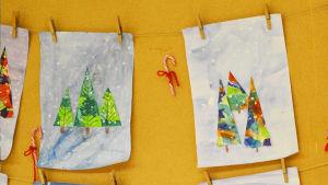 Teckningar på julgranar hänger på en anslagstavla.