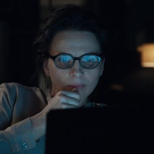Juliette Binoche som Claire sneglar på sin datorskärm i mörkret.