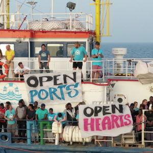 """En bild på båten Sea Watch med flyktingar ute på däcket med skyltar där det står """"open ports"""" och """"open hearts""""."""