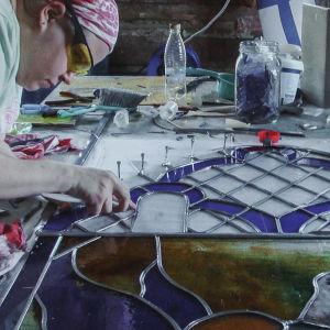 Nainen tekee lasimaalausta kirkkoa varten.