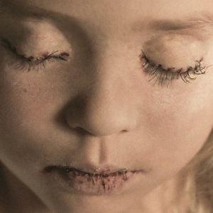 Lapsinäyttelijän kasvoille on kiinnitetty lankaa esittämään tikkejä, hänen suunsa ja silmänsä on ommeltu kiinni.