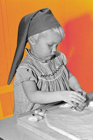 Kuvassa on kaksi lasta tonttulakit päässä leipomassa vuonna 1958