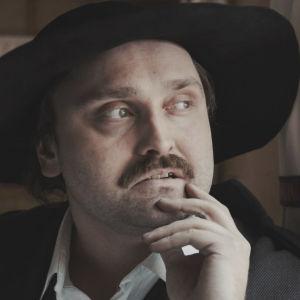 Man i svart hatt med stort brätte lutar hakan mot sin hand och tittar ut genom fönstret.