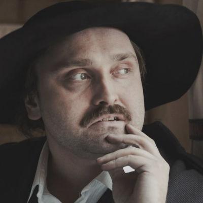 Isolieriseen mustaan hattuun pukeutunut viiksekäs mies, näyttelijä Sami Sainio, pitää kättään leualla ja katsoo ikkunasta ulos.