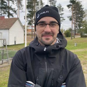 Hiihtäjä Risto-Matti Hakola seisoo syksyisen urheilukentän edessä.