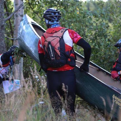 Kolme seikkailukisan osallistujaa kantaa kanoottia kaislikossa.