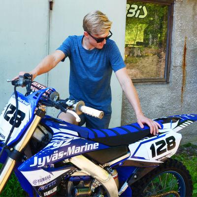 En ung man håller i en blå motorcykel.
