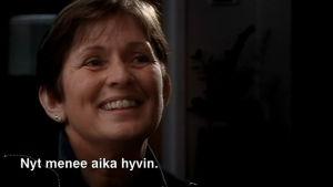 Nainen puhuu ja hymyilee