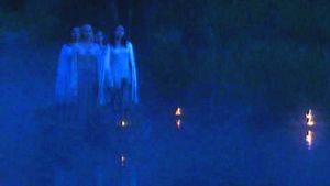 Kvinnor som går i mörker bland ljus