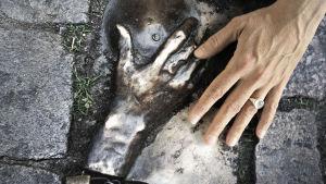 ihmisen käsi koskettaa pronssikättä