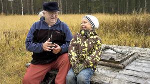 Mies ja poika istuvat kaivonkannella juttelemassa
