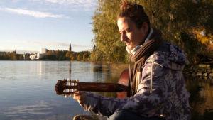 Mies virittää kitaraa Töölönlahdella