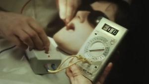 En tandläkare mäter ström i munnen på en patient