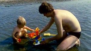 Isä leikkii lapsensa kanssa rannalla (1988),