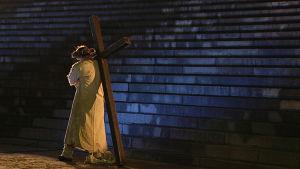 En man bär på ett kors.