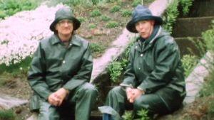 Aagot Jung och Udo Drude sitter iklädda regnställ i ösregn och diskuterar stenpartier