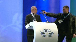 En man riktar ett vapen mot Ahmed Dogan.