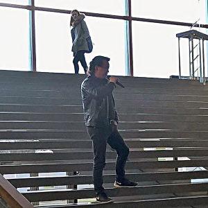 Nahkatakkinen mies mikrofinin kanssa Tampereen yliopiston portailla